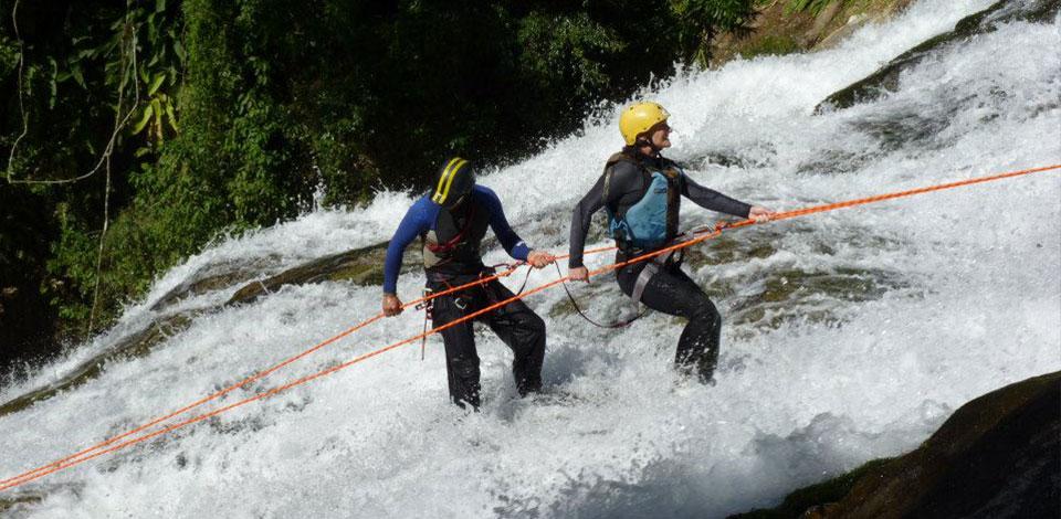 duas pessoas praticando rapel em cachoeira