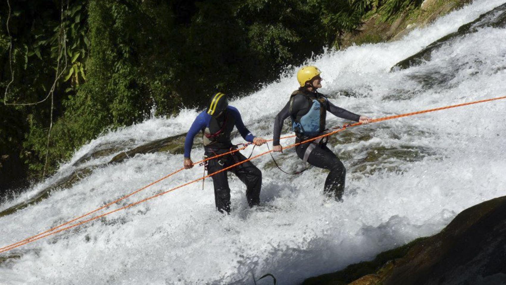 duas pessoas fazendo rapel de cachoeira