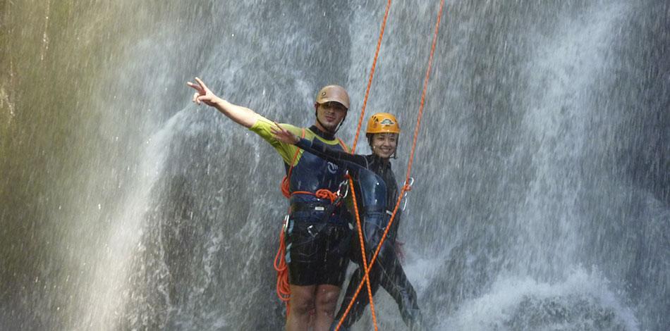 duas pessoas praticando rapel em cachoeira no circuito de aventura